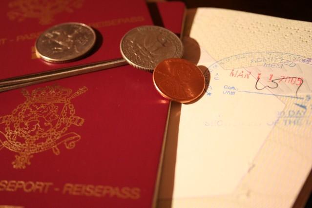 Pár mincí ležících na cestovních pasech